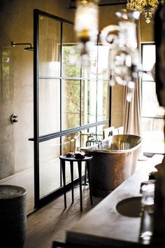 In love with this bathroom in a safari lodge in Kenya – copper bathtub, chandelier and steel-and-glass windows as a shower screen