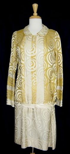 20s gold and cream silk damask summer day dress features a striking swirl pattern woven into the lustrous fabric, as well as the sporty, lean, hip-cinched silhouette so popular in mid- to late 20s dresses. The round collar has a two snap closure, concealed beneath the faux button placket with its long row of trios of mother of pearl buttons; cuffed sleeves have a snap closure as well