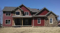 New construction. Red siding. Stone. 2 story. www.SuppesHomes.com