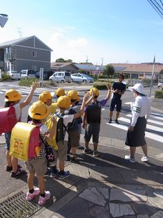 Japanese children are briefed to have their hands up to appear taller to motorists, look left, look right and look left again.  You might also see them wearing bright yellow hats or carrying yellow flags.