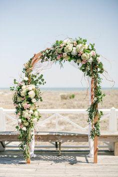 arche mariage décorée de verdure et de fleurs roses et blanches, mariage au bord de la mer
