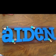 Wooden letters painted and glued on wooden frame and buttons added