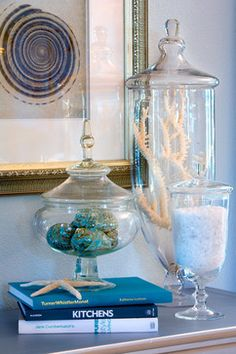Pretty beach vignette - shells, sand, starfish are all dressed up in pretty apothacary jars, gold framed shell artwork, and books to match and add some interest.