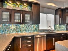 An ocean glass backsplash makes a beautiful design statement. Designer Shirry Dolgin continues the backsplash above the frosted glass cabinets to maximize its impact.