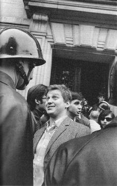 """Mai 68-Veston ouvert sur sa chemise à carreaux, Daniel Cohn-Bendit rejoint un groupe de gardes mobiles qui fait le pied de grue devant la Sorbonne. Ce 6 mai 1968, """"Dany le rouge"""" est convoqué devant le conseil de discipline de la vénérable université,avec six autres étudiants.  Le jeune rouquin se retrouve nez à nez avec un agent casqué. Fossettes impertinentes, l'étudiant plante progressivement son regard narquois dans celui du garde mobile."""