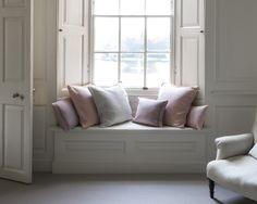 Cute window seat with beautiful shutters and some lovely cushions.