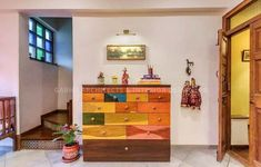 Storage Unit can be Designed as an ✨ Art. Here there is a play of Geometry & Colours which is making it an Art Piece. Storage Space is also a Display Area of Arts in your Home. Hanging Traditional Rajasthani Dolls and Artifacts on the Storage Top is giving an Artistic Touch to the whole Space. Pot with beautiful 🍃 Plant is adding Freshness to Space - GharPedia Storage Spaces, Storage Units, Geometry, Art Pieces, The Unit, House Design, Colours, Display, Traditional