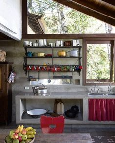Cozinha rústica com bancada construida em alvenaria (cimento queimado) e muito vidro para iluminação natural.