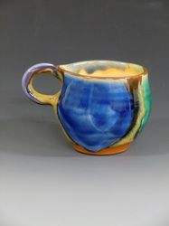 """From Julia Galloway's Library of Cups project: This cup embodies the best of the best of what low fire clays and glazes are. The richness of the clay exposed on the bottom of the cup; the laying of slips and glazes is so masterful that it looks effortless. Joan Bruneau makes a living from her pottery in Nova Scotia, and continues to product pottery of great vibrancy and satisfaction."""""""