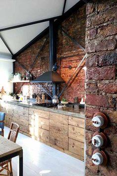Грубая кирпичная кладка, фасады кухни из плохо обработанной старой доски, металлические балки создают дух стиля лофт.