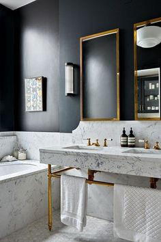 Stylish inspiration for bathroom vanity units and cabinets including this Marble Double Vanity with Brass Accents in a bathroom with blue-black walls.