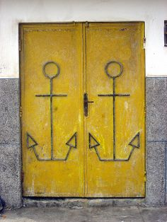 These nautical doors are one in a million! Bright yellow doors w/ anchor embellishments stand out against the stark facade of cement & stone.