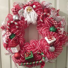 Santa Clause Christmas Deco Mesh Wreath  This handmade wreath was made using a red deco mesh material with a white stripe running through it and is decorated with a Santa Clause head, different ribbons and assorted Christmas ornaments. This wreath is approximately 24-26 inches in diameter and is perfect for your door for the Christmas holiday and winter season.