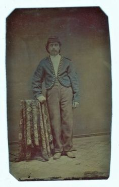 CDV sized tintype of a Civil War era Zouave.  Soldier wears matching red trousers and kepi, dark blue jacket with shoulder boards and ball button trim. Image was found in Michigan.