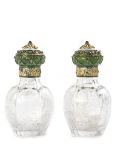 A pair of Fabergé jewelled and guilloché enamelled varicolored gold-mounted glass scent-bottles, workmaster Henrik Wigström, of circular bulbous form, each bottle finely engraved with floral branches within arched panels, the lift-off cover enamelled in green, yellow and oyster white guilloché enamel with applied gold foliage scrolls, swags and branches set with diamonds, surmounted by cabochon garnet finial.