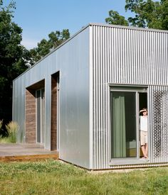 Hints of the interior wood palette are visible from outside the house, creating a rich edge for the corrugated metal facade. Perforations...
