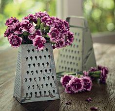 Flores no ralador: o utensílio cobre um pote com água para manter as flores fresquinhas e viçosas.