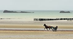 A jockey and his horse train on the beach, as WW II ship wreckage is seen in the background at Utah Beach. Traces of World War II can still be found all across this stretch of Normandy. (AP Photo/Remy de la Mauviniere)