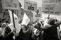 """July 12, 1964. """"Ku Klux Klan members supporting Barry Goldwater's campaign for the presidential nomination at the Republican National Convention, San Francisco, California, as an African American man pushes signs back."""" 35mm negative by Warren K. Leffler for U.S. News & World Report."""