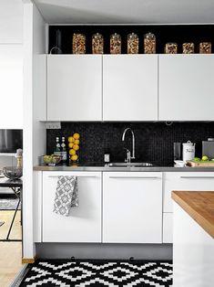 Aiempien asukkaiden remontoima keittiö on Riinan ja Peltsin mieleen, juuri tällaisen saarekekeittiön he itsekin olisivat tehneet. Musta taustaseinä tuo kontrastia valkoisille kaapistoille. Keittiön kaapistot ovat Puustellilta, matto Svaneforsilta.