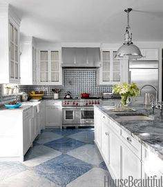 The marbleized painted floors in the kitchen look great and hide scuff marks. An industrial-style pendant by the Foundry complements the Wolf range and hood.   - HouseBeautiful.com