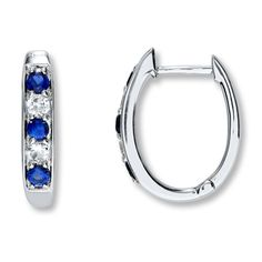 Alternating blue and white round lab-created sapphires line these stylish hoop earrings for her. Set in sterling silver, the earrings are secured with hinged backs.