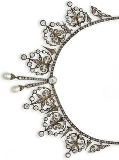 Diamond & pearl necklace/tiara/brooch combination, circa 1890 The chain of old brilliant & single-cut diamonds, with a large cushion-shaped diamond to the centre, terminating in a similarly cut diamond and drop-shaped pearl tassel of unequal length, suspending either side a graduating fringe of stylised heart-shaped pendants with foliate detail, alternating with dart motifs, set throughout with old brilliant & rose-cut diamonds, mounted in silver & gold.