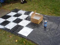 Halloween 2009 Decor working on checkered floor mat (used bottomless box frame on black plastic and 99.cent can of white spray paint. Floor piece 10ft x5ft. To go into down the hole tunnel)