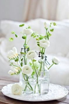 Beautiful white flowers in vintage bottles...just lovely. What's in there? Ranunculus, Freesia ... What's the green filler? Is it just the greenery of the ranunculus or is it something else?