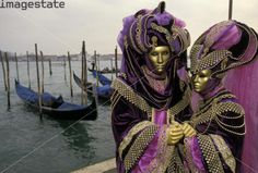 COUPLE IN VENETIAN CARNIVAL COSTUMES WITH GONDOLAS IN BACKGROUND. Location: VENICE, ITALY