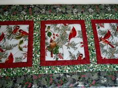 Beautiful fabrics from the Winter Magic collection from Hoffman are featured in this quilted table runner, for your winter and holiday decorating. The silver metallic highlights add a touch of elegance. The double fold binding is machine stitched and hand sewn on to the backing, which is an ivory floral print. Machine quilted. Table topper measures 18.5 x 41. Nicely sized for a side table, coffee table or buffet, to feature a candle or holiday decoration on.  Machine wash gentle, warm…