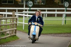 A groom (and his bestman) arrive in style on a moped  during his wedding at Fontwell Park near Chichester, West Sussex, UK. Photo by Scott Ramsey Photography