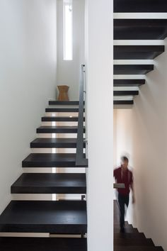 This set of modern stairs lead up to the sleeping areas of this house. Dark wood treads are a strong contrast to the white walls.