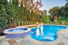 Sparkling glass tile encircles the freeform pool's waterline and the raised spa that also doubles as a water feature. Platinum Poolcare, Ltd; Outvision Photography http://www.luxurypools.com/builders-designers/platinum-poolcare-ltd.aspx