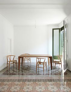 Original floor tiles were relocated to highlight seating areas during designer Laura Bonell Mas' renovation of this Barcelona apartment.