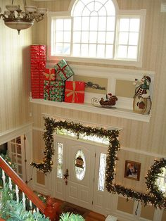 This is interestin how they placed wrapped boxes on the ledge in the foyer.  Foyer Christmas Decor