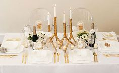 Inspired by Glittering Gold Wedding Ideas (anemone, centerpieces, cream, elegant, navy blue, glamorous, gold, place settings, silverware, candles) — Loverly