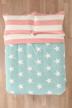 Duvet cover crafted from soft cotton topped with an American flag print and paired with American Flag Shams in pink and aqua from Urban Outfitters.