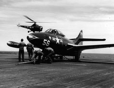 Sailors work with a tow bar attached to an F9F-2P...