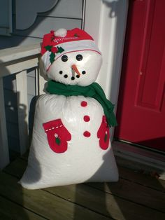 I got this idea from the pillow case snowman I saw here on Pinterest...only I made mine out of doubled small and tall kitchen trash bags, a dollar store Santa hat , some pompoms, fleece scraps, big buttons for eyes, puffy paint and bean bag filler. (Oh, and a baggie of sand/dirt...or a couple bricks would work too....to weight him so he would`nt blow away in a winter storm!)
