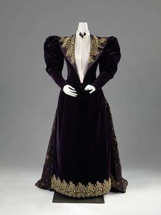 Dress with Appliques, Hirsch, c.1893. In the 1890s ladies wore dresses with large gigot sleeves that made the shoulders look broader and the waistline smaller. In this period, skirts were wider at the back, an effect here further enhanced by the train. The dress resembles a costume tailleur, an outfit consisting of a jacket and a skirt. The blouse is a false shirt front. The decoration is a striking combination of appliques and woven floral motifs.