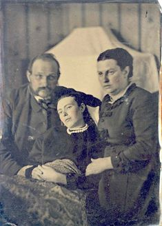 Post-mortem photo of parents with their daughter -- notice they are a bit blurry from slight movement, but she is perfectly clear...