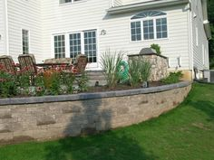 The retaining walls for this raised patio create beautiful planters with custom landscaping.
