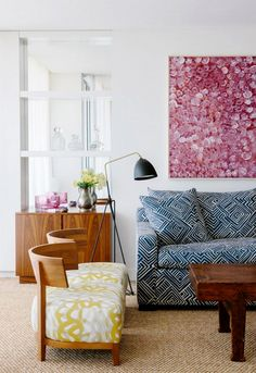 White living room with colorful art and blue sofa