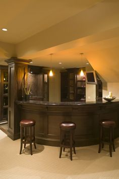 A curved bar area with subtle dark granite and a low-pile carpet. A small step leads into the bar area, which is filled with plenty of cabinet space and a mosaic tile backsplash behind the sink.