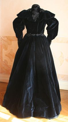 Complete three-piece (bodice, skirt and cape) in velvet dark blue silk. The bodice is closed in front by hooks. Inside the cape there 'label' paves daughters Grace M. Mode and Packaging Naples, 1891-1900. Dress, back view without cape