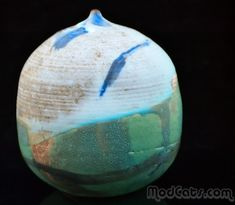 Toshiko Takaezu super cantelope sized rattle vase from her Makaha Blue series. Glaze treatment is very abstract with splashes of green, brown, light, medium and electric blues. Signed on the bottom with the artist's cipher.