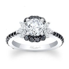 This unique white gold black and white diamond halo engagement ring features a prong set round diamond center encircled with black diamonds and accented with white marquise cut diamonds for a stunning alternative to a traditional halo ring. A slightly squared shank helps to keep the ring from turning on the finger. Also available in rose yellow gold 18k and Platinum.