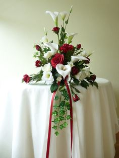 A traditional, triangular arrangement featuring calla lilies with red roses and trailing ivy.