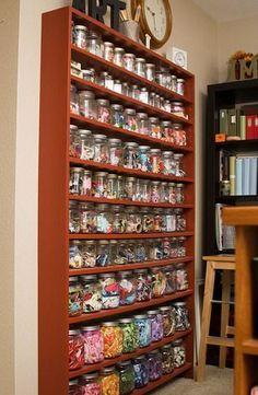craft supplies in mason jars on skinny bookshelf